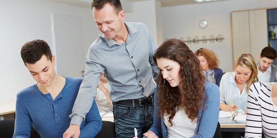 Mężczyzna - nauczyciel pokazuje uczniom coś w ich zeszycie