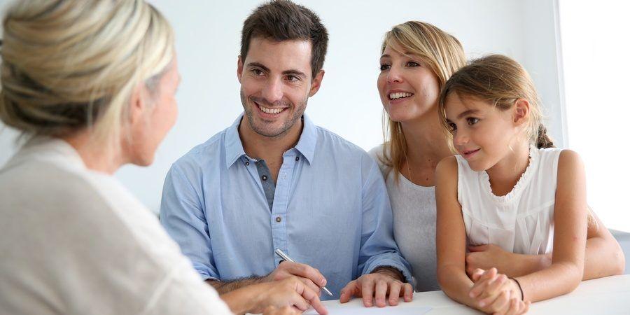 Uśmiechnięte twarze rodziców z córką na spotkaniu z gościem