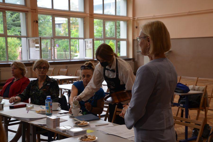 Uczennica lu uczeń podaje uczestniczce spotkania kawę